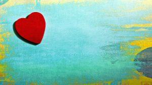 Kuvassa on puisella pöydällä puinen sydän.