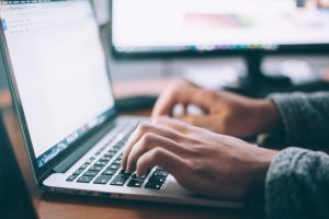 kädet näppäilevät kannettavaa tietokonetta.